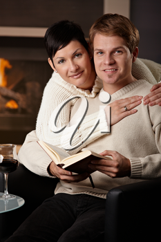 Happy young couple hugging in front of fireplace at home, looking at camera, smiling.