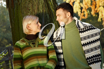 Young couple looking at each other, smiling, in sunny autumn background.
