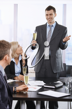 Happy businesspeople celebrating sussess at office, smiling businessman raising toast with champagne flute.