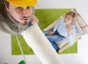 Man in focus standing on ladder using paint roller, woman in background sitting in armchair, looking up. Overhead shot  focus placed on roller.