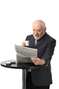 Portrait of happy senior businessman drinking coffee reading newspaper, laughing, white background.