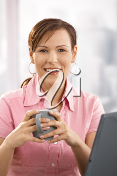 Happy businesswoman drinking coffee at desk, looking at camera, smiling.
