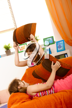 Small girls having fun in pillow fight on couch, laughing.