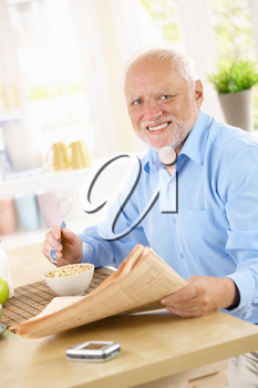 Portrait of older happy man at breakfast table, having cereal, reading papers, smiling at camera.