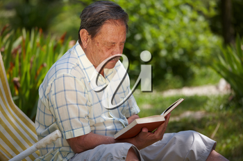 Healthy looking senior man is his late 70s sitting in garden at home and reading book, outdoor.