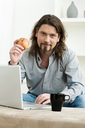 Casual man using laptop computer at home, sitting at couch, holding apple.