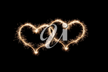 Two hearts a love symbol made by sparklers on a black background.