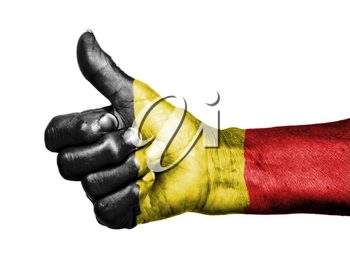 Old woman with arthritis giving the thumbs up sign, wrapped in flag pattern, Belgium