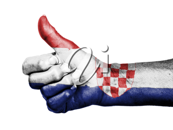 Old woman with arthritis giving the thumbs up sign, wrapped in flag pattern, Croatia