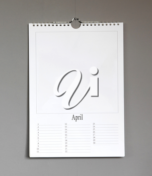Simple old birthday calendar hanging on a grey wall, copy space - April