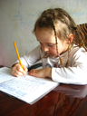 the little girl with nice hair-do learning her  home tasks