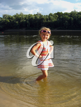 little girl standing in the beautiful river