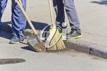 Photo of two men legs cleaning street with broom and shovel