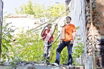 Father and teenager son are standing in ruins