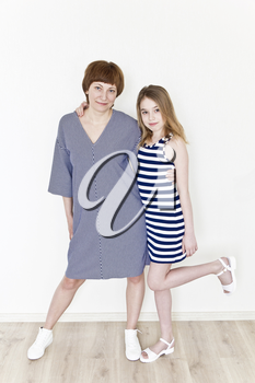 Happiest mother and daughter playing near white wall in striped clothes
