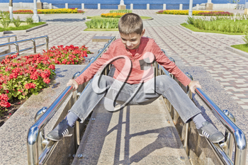 Teenager boy exercise at embankment in summer