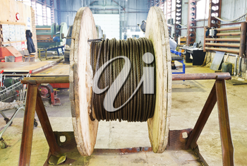industrial wooden reel with steel rope in mechanical workshop