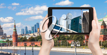 travel concept - tourist photographs picture of Moscow City on tablet pc