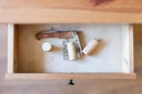 above view of foldable corkscrew and few corks in open drawer of nightstand