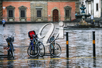 travel to Italy - wet bicycles on piazza della santissima annunziata in Florence city in winter rainy day