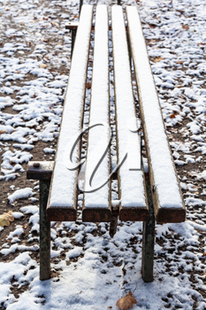 surface of wooden bench covered with the first snow in urban park in frosty autumn day