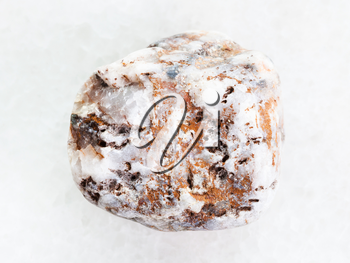 macro shooting of natural mineral rock specimen - marble pebble on white marble background from Greece
