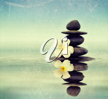 Vintage retro hipster style travel image of Zen spa concept background - Zen massage stones with frangipani plumeria flower in water reflection with grunge texture overlaid