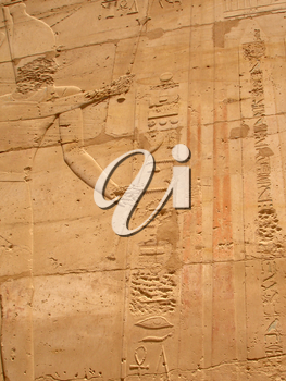 Old wall in the Karnak temple with ancient images.