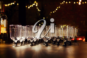 Empty wineglasses on holiday reception table in night-time lighting.