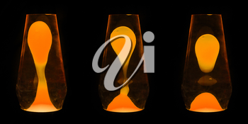 Three lava lamps showing progress of the Orange wax yellow up and separating