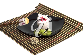 white cake together with a kiwi on a rug, with chopsticks