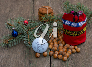 coniferous branch with Christmas tree decorations, a red gift bag and nutlets, the subject Christmas and New Year