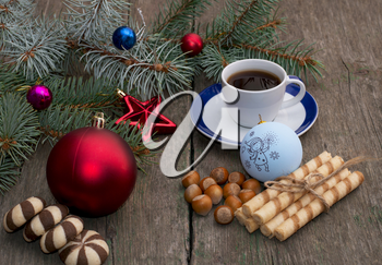 fir-tree branch with Christmas tree decorations, coffee, different baking and nutlets, a subject holidays Christmas and New Year