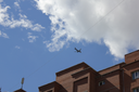 Silhouette of plane above building against the blue sky 18543