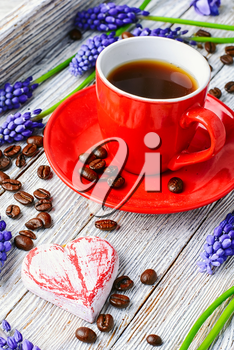 Red coffee cup on a wooden tray covered with flowers of hyacinth