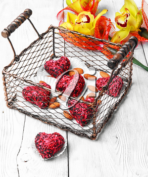 Stylish metal basket with candies in shape of heart and bouquet of orchids