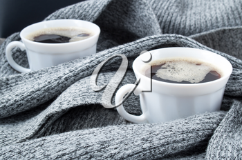 Two white cups of coffee wrapped in folds of gray woolen scarf with a small depth of focus