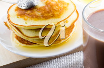 A mug of hot cocoa and pancakes with honey close-up with shallow depth of focus