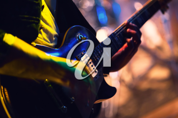 Colorful blurred rock music background, guitar player on a stage with colorful illumination