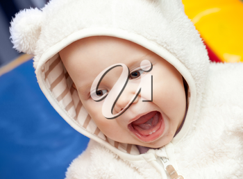 little baby laughs with open mouth in white bear costume
