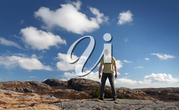 Young man staring at blue sky stands on rocky ground