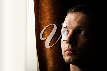 Young Caucasian man looking in bright window, closeup portrait