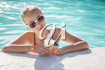 Little blond girl with glass of cocktail in a swimming pool