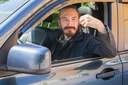 Smiling Asian man with keys as a driver of modern Japanese suv, outdoor portrait in open car window