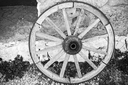 Old wooden wheel stands near stone rural wall, black and white retro style photo