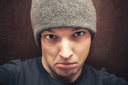 Young agressive Caucasian man in gray hat. Close-up studio face portrait over dark wooden wall background, selective focus