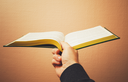 Male hand holds open book, vintage toned photo with selective focus