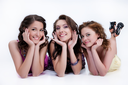 Three young smiling women lying on a studio background