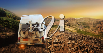 White truck with mountain bike in the mountain at sunset