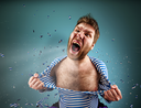 Furious man is tearing clothing on himself and are screaming